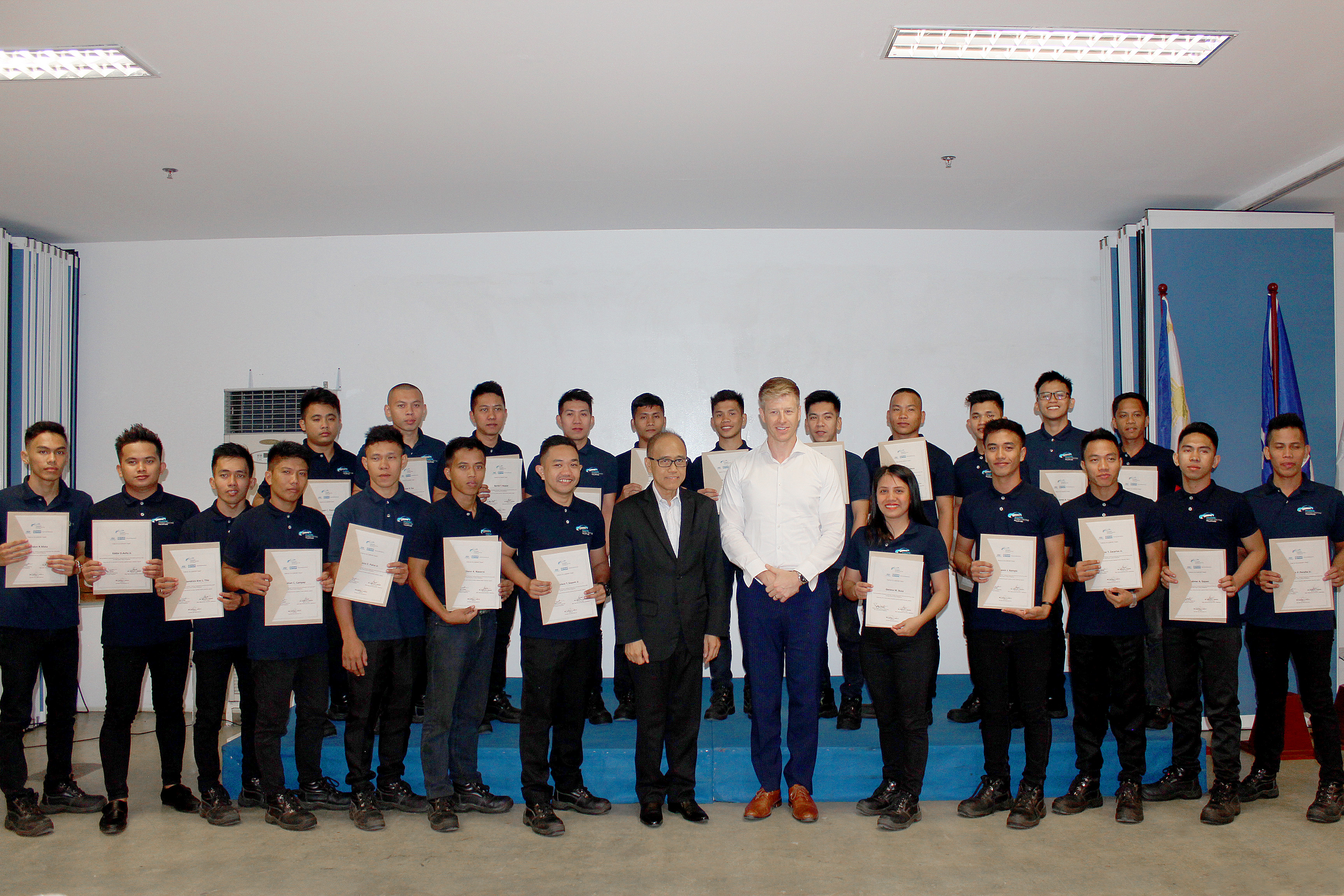 Hyundai Dream Centre Philippines' second batch of Course 3 automotive technology graduates show off their diplomas with HARI Chief Finance Officer and Chief Operating Officer for the Corporate and Trade Operations Support Services Group, Ladislao Avila and Plan International Deputy Country Director-Programme, Ryan Lander.